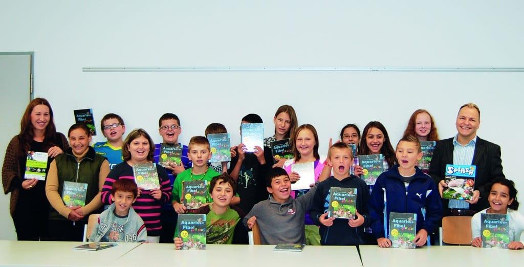"""Das Kinder- und Jugendmagazin """"SPLASH"""" und die """"Aquaristik for Kids"""" Fibel aus dem Dähne Verlag fanden Klassenleiterin Martha Scherner (links außen) und die Schüler toll und stellten dem Förderer (rechts außen) Fragen über Fragen zum Thema."""