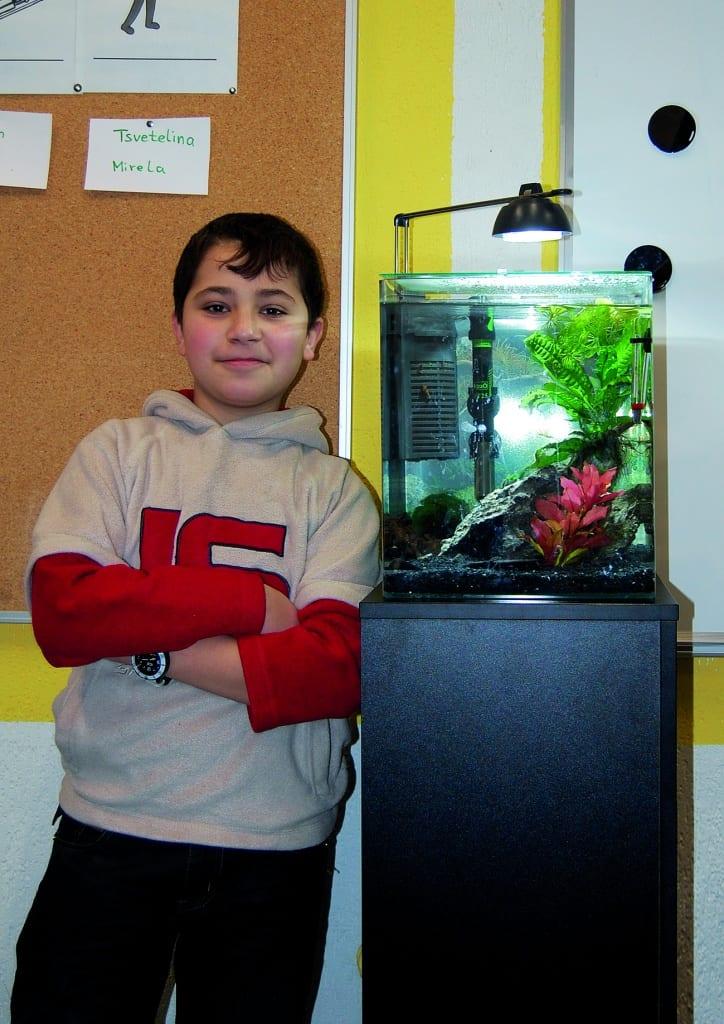 Zwei Wochen nach dem Einrichten des Nano-Beckens besuchte Michael J. Schönefeld wieder die Klasse um zu sehen wie sich das Aquarium entwickelte. Hier steht einer der Schüler ganz stolz neben dem Aquarium.